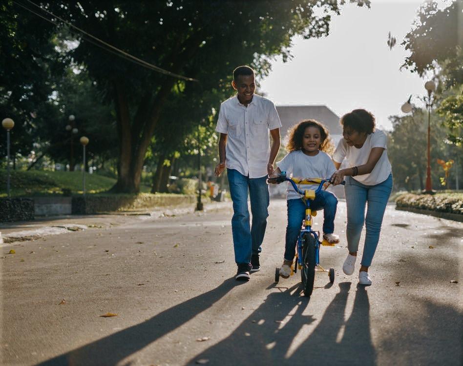 parents teaching kid to ride a bike